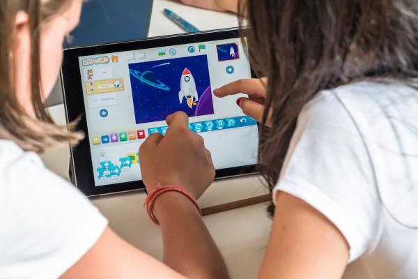 Zwei Schülerinnen entwickeln ihr Programm in ScratchJr